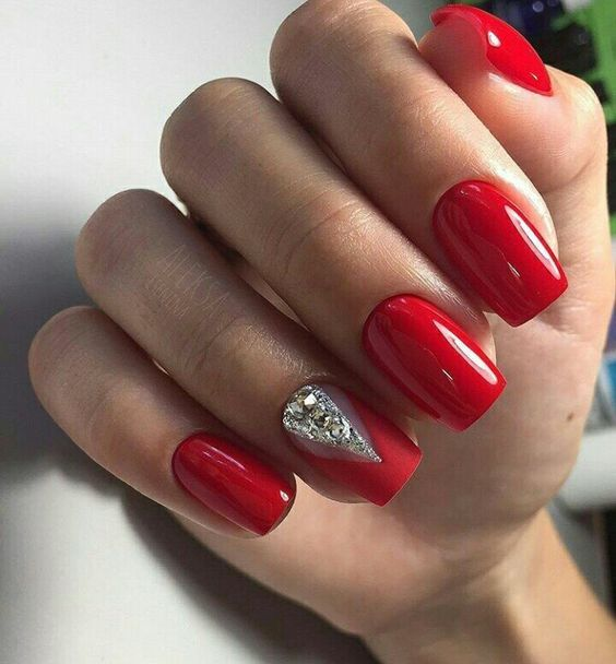 Red Nails And An Accent Matte Nail With Large Rhinestones