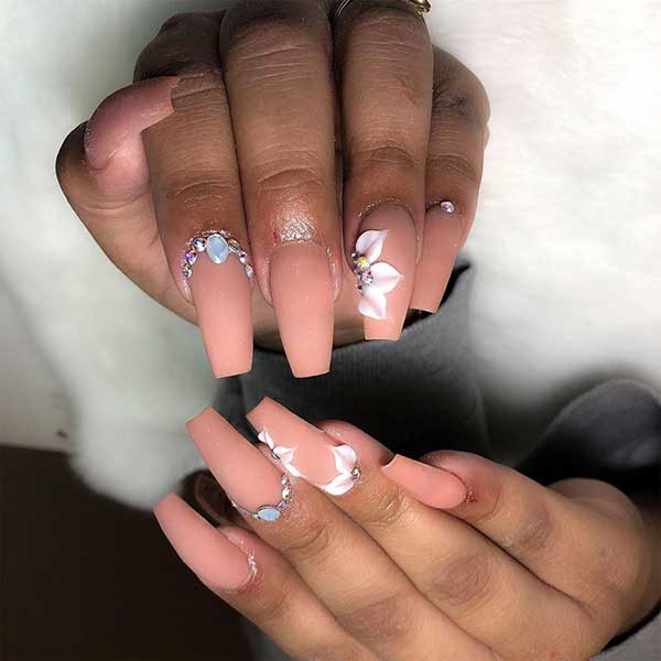 Beautiful matte nude coffin nails with rhinestones and an accent floral nail!