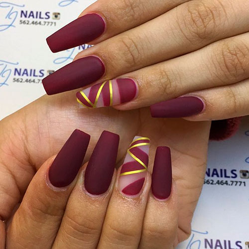 Cute matte burgundy coffin nails with gold striped accent nail!