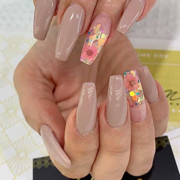Cute nude coffin nails with an accent floral nail with glitter design!
