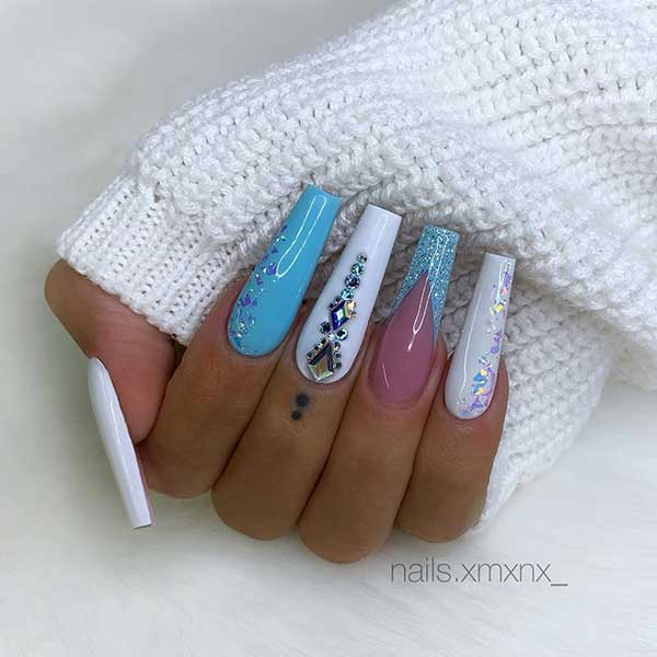 Cute white coffin nails with light blue nail & light blue glitter French tip design which adorned with glitter and rhinestones!