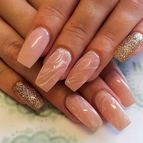 nude marble coffin nails with a little glitter and one nude nail and one gold glitter nail!