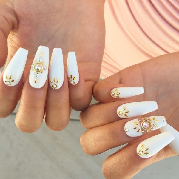 white and gold coffin nails adorned with rhinestones & goldy embellishments