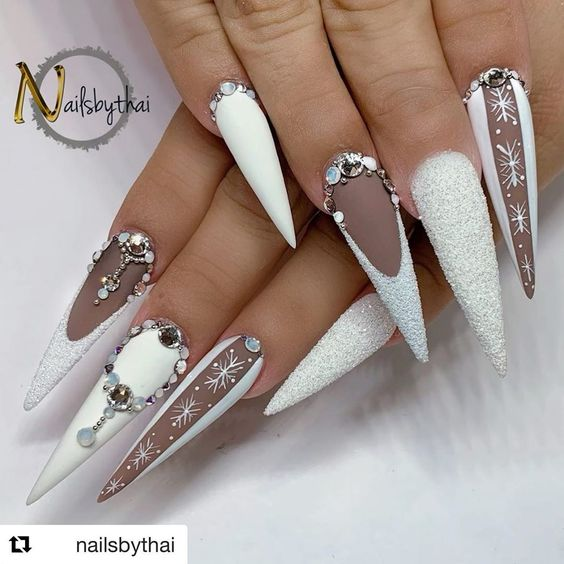 Cute white winter nails with white glitter, rhinestones, and snowflakes!