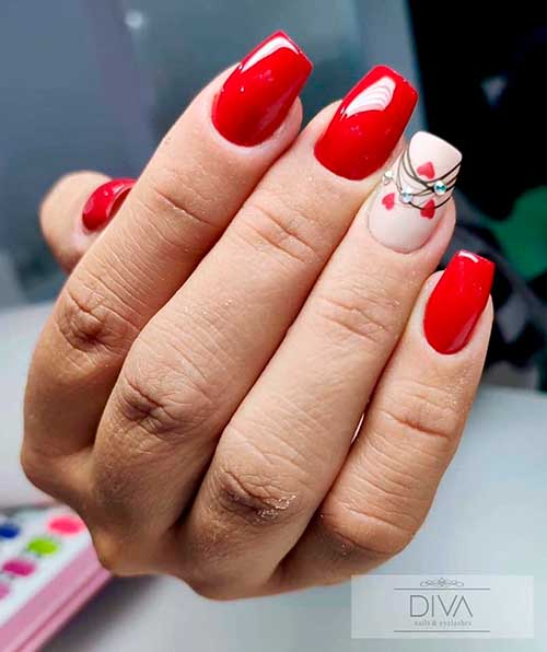 Red valentines day nails coffin shaped with accent nude nail adorned with red hearts and rhinestones